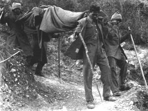 Indian stretcher bearers carry a badly wounded man at Cassino